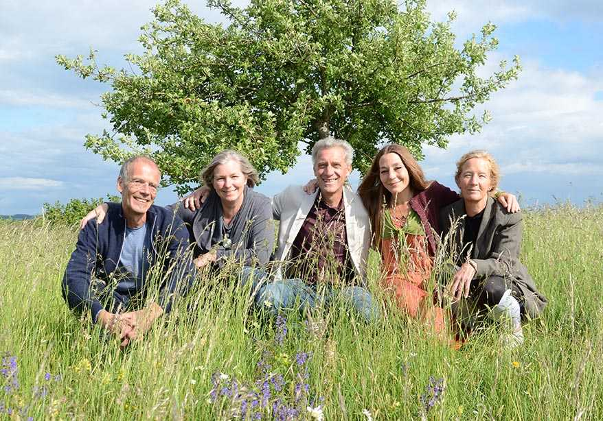 Five people squat on a meadow with high grass, in front of an apple tree and blue sky