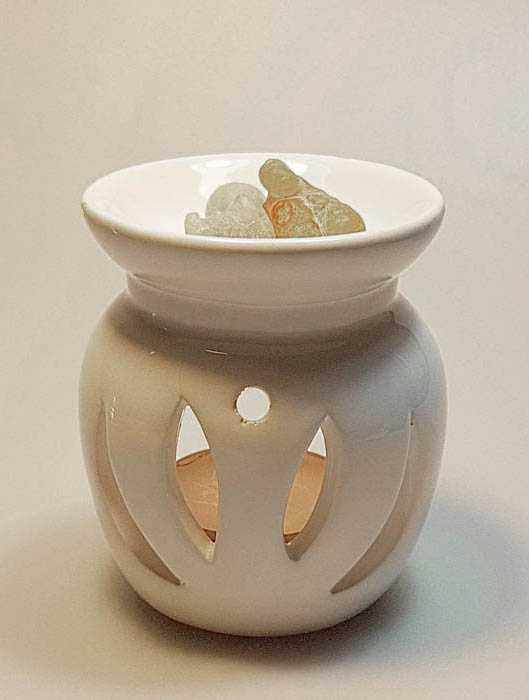 Weisse Duftlampe mit Weihrauch und goldenem Kerzenlicht