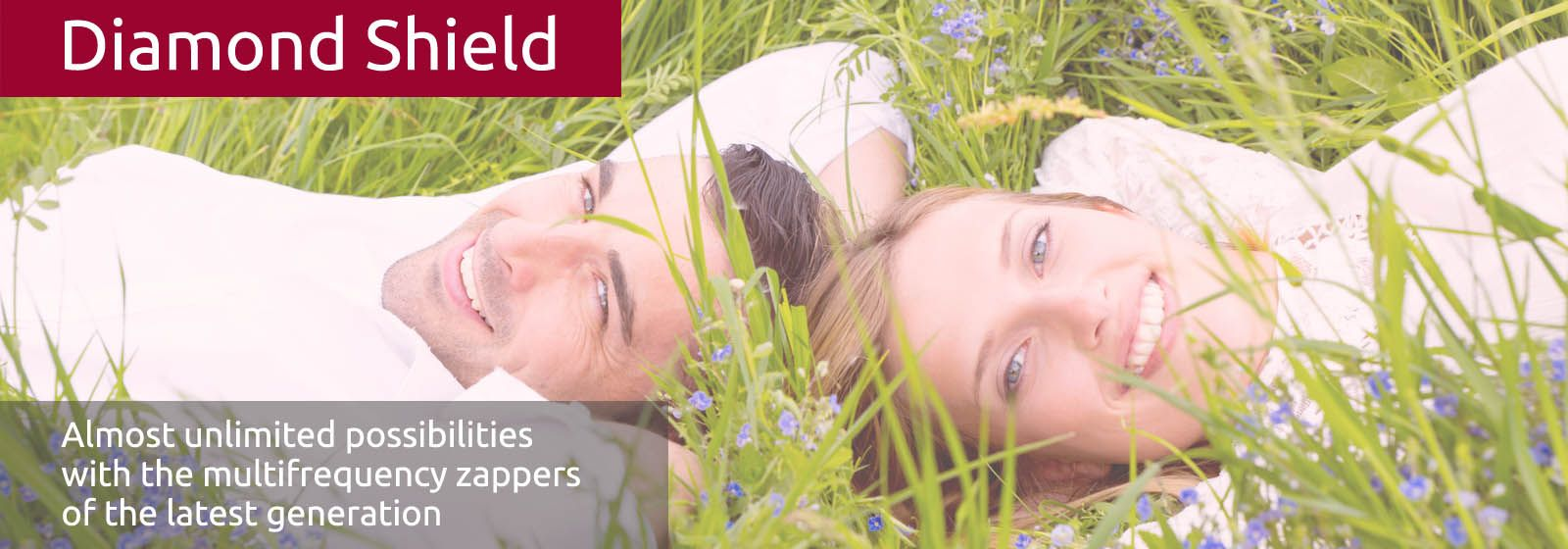 A young couple lies head to head smiling in the grass